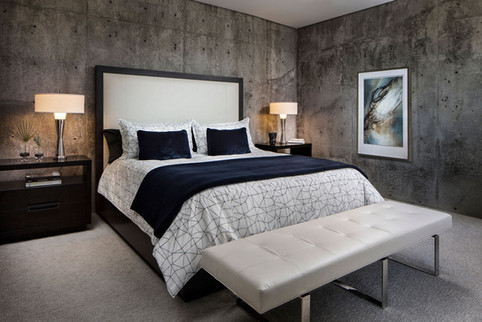 Modern Oasis bedroom with concrete walls, blue, grey and white accent colors, leather end of bed bench, tall upholstered headboard, and chrome lamps