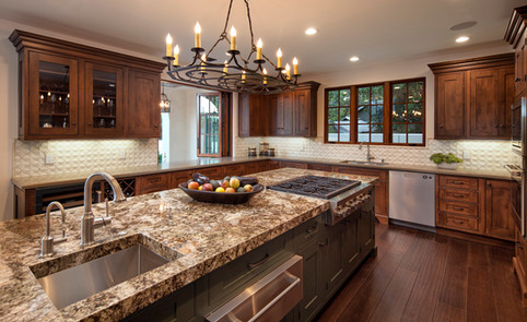 Spanish Mediterranean Elegance kitchen with custom dark wood cabinets, granite countertop, kitchen island, iron island chandelier stainless steel appliances, wood floor, pass though kitchen window