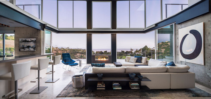 Modern Oasis Modern living room with double height glass walls, fireplace, Italian leather sectional with built in bookcase, white bar stools, blue modern chair, and concrete walls in California