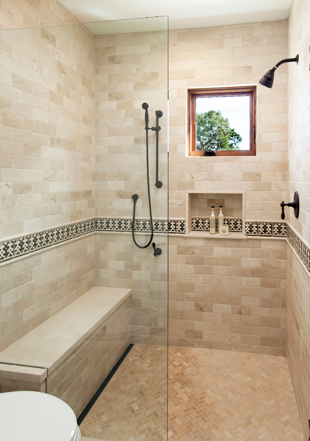 Spanish Mediterranean Elegance bathroom with limestone tile walls, bench, infinity drain, hand painted tile