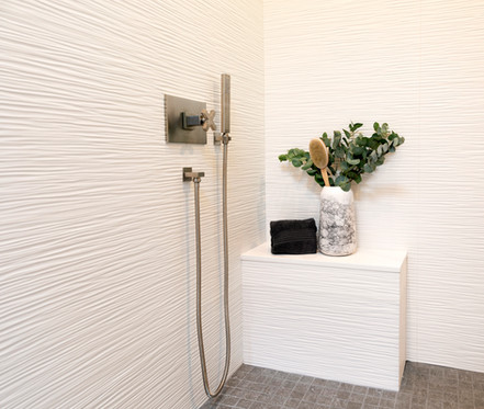Shower with white 3-dimensional wall tile and built in shower bench