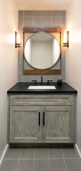 Powder bathroom with grey vanity cabinet, round mirror and patterned tile on floor and wall.