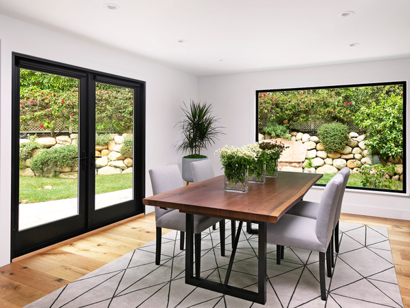 Dining room with white walls, black painted doors and windows, live edge dining table, graphic area rug