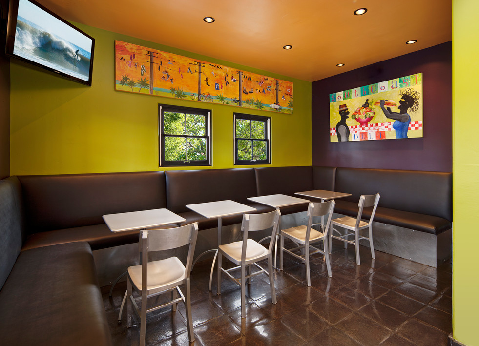 Colorful Deli seating area with green, orange and purple walls and banquette seating