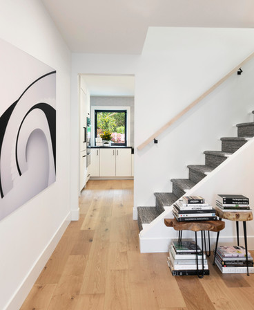 Hallway with white walls, stairway with carpet runner, light oak wood flooring. Stools with stacked books.