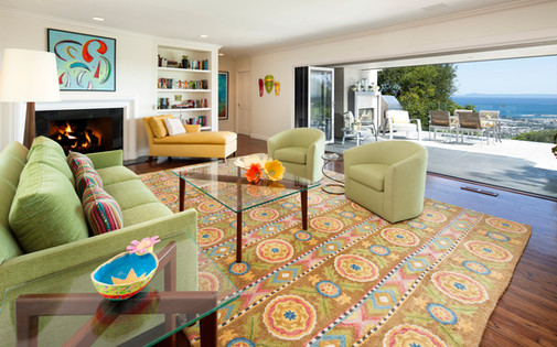 Colorful modern living room interior design in Santa Barbara with green sofa and green chairs. Nana walls opening to ocean view patio.