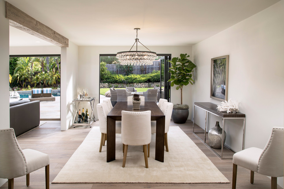 Elegant California Ranch White painted dining room with light oak floors large window and modern crystal chandelier