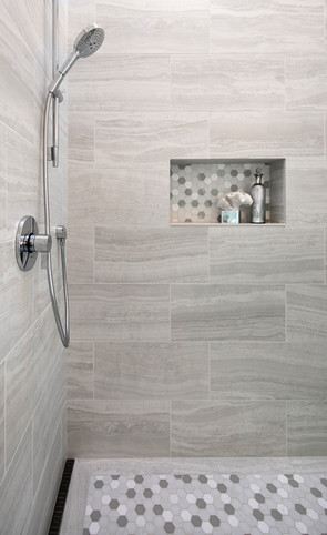 Walk in shower with infinity drain, mosaic floor tile, grey porcelian wall tile and shampoo niche