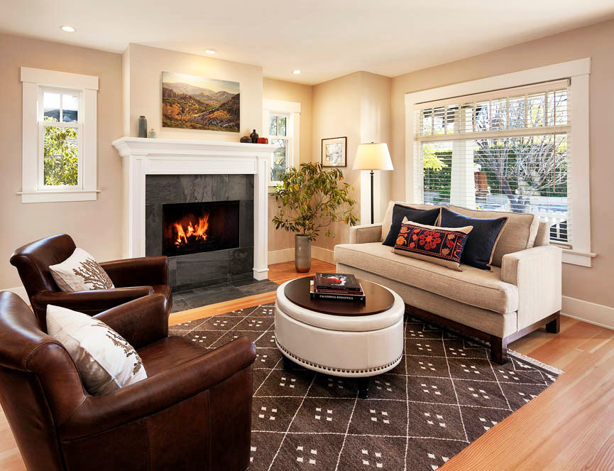 Cozy living room with warm, neutral colors, brown rug, leather chairs, beige sofa and ottoman. White wood fireplace.
