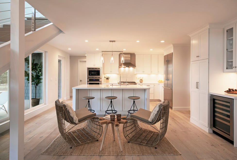 Beachy white kitchen and island with seating area with rattan chairs and stool on sisal rug