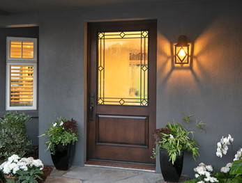 Custom stained wood front door with glass and iron, custom iron wall lantern exterior lighting on grey stucco house
