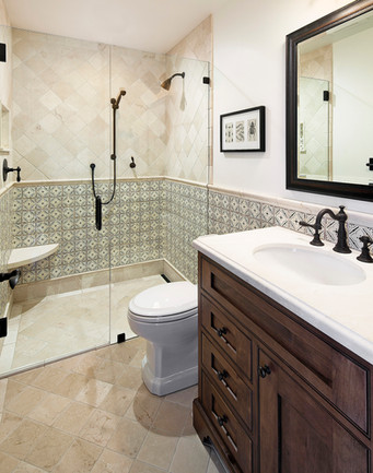 Spanish Mediterranean Elegance guest bathroom with hand painted tile wainscotting and limestone tile