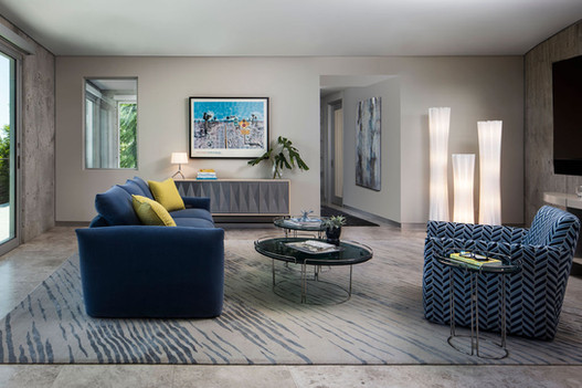 Modern Oasis Modern den interior design with blue sofa and blue herringbone chair with yellow accents.