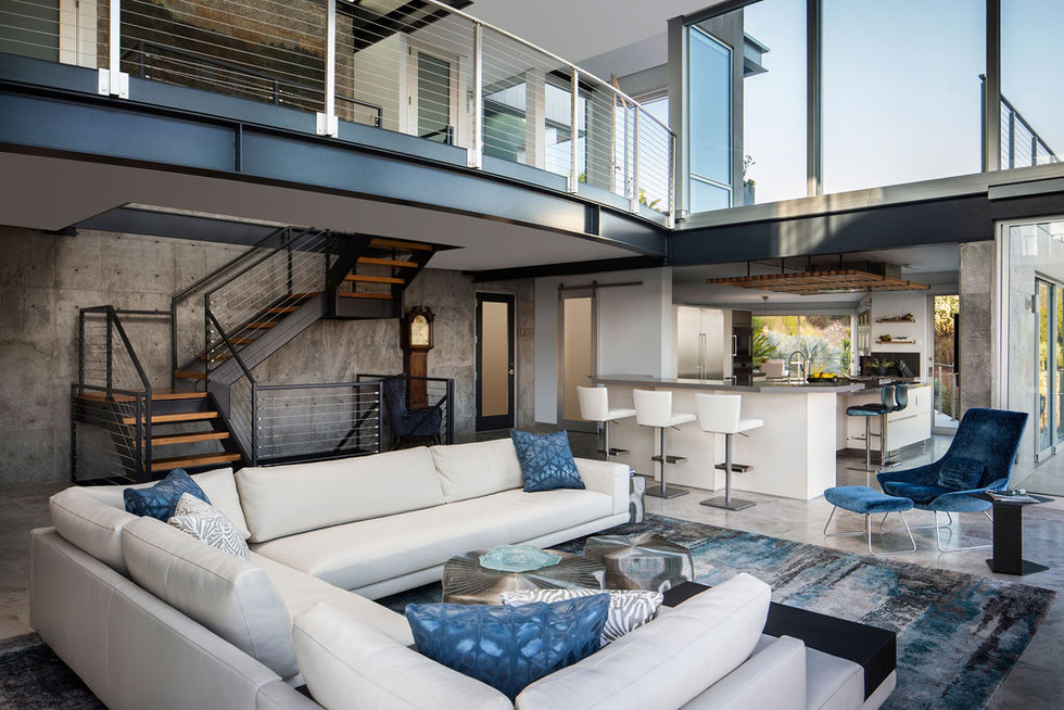 Modern Oasis living room and kitchen with concrete walls, steel staircase, double height glass walls, white and blue furniture and mezzanine walkway
