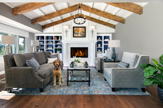Wine Country Living interior designer living room with white wood fireplace and built in bookshelves, designer sofa, armchairs and blue rug on wood floor. Vaulted ceiling with wood beams