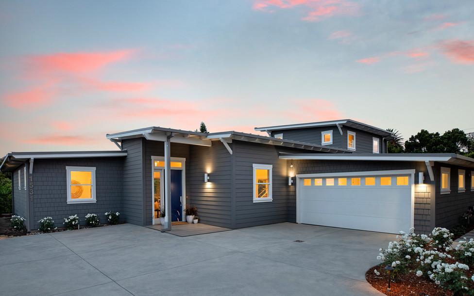 Modern beach house with dark grey siding and white garage door