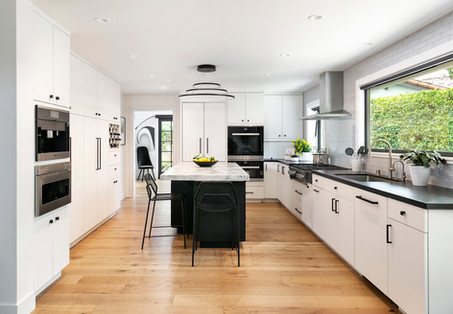 Modern kitchen with white cabinets, black countertops and black cabinet hardware, black island with marble top. Built in appliances. Light oak wood floor.