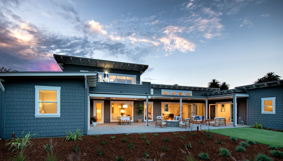 Backyard and rear facade of modern beach house with large bifold doors and indoor/outdoor living