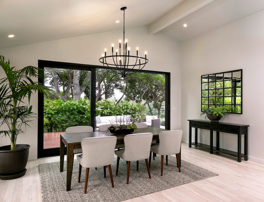 Modern dining room with vaulted ceiling, white walls, light oak wood floors and iron chandelier