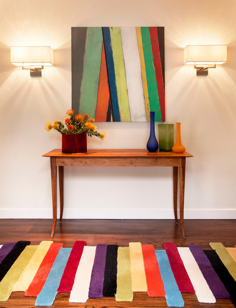 Wood console table with colorful modern runner rug and odern artwork
