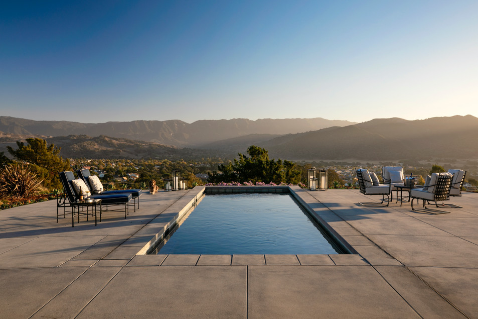 Residential patio with swimming pool, outdoor furniture, mountain view