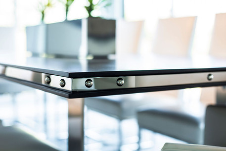 Modern Oasis Up close details of metal strap on wood dining table