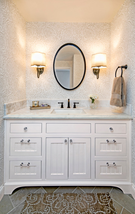 Wine Country Living Powder bath white wood vanity cabinet with beige floral wallpaper and oval mirror with sconces