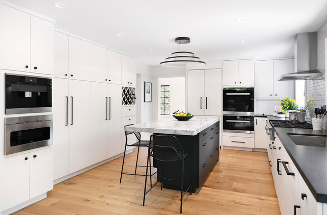 Custom modern white kitchen in Santa Barbara with contrasting black island. Stainless steel appliances, built in wine rack and coffee maker