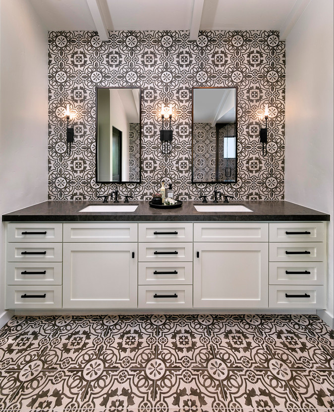 Master bathroom white double sink vanity with pattern tile floor and backsplash wall and black countertops