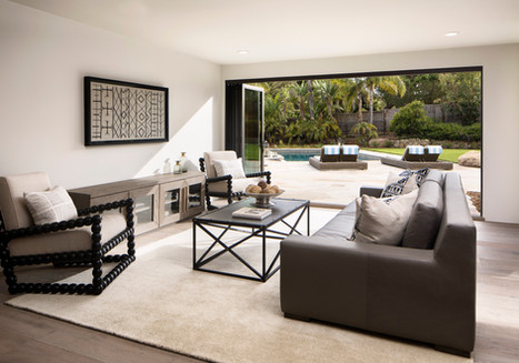 Elegant California Ranch Painted white living room with indoor/outdoor access to backyard