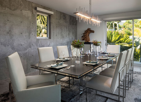 Modern Oasis Modern dining room interior design. Wood table with metal strap detail, white leather sleigh chairs, concrete walls and horse statue