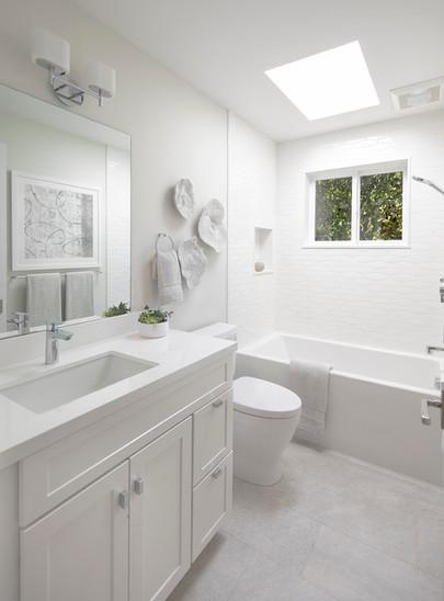 White, modern coastal bathroom with skylight