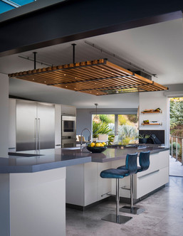 Modern Oasis kitchen island with white cabinets, blue swivel barstools