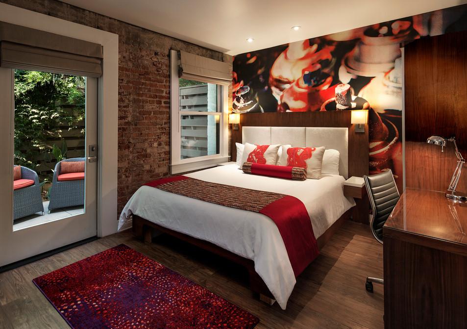 Hospitality interior design in Santa Barabara with bright carpet and bedding, wallpaper accent wall and brick wall