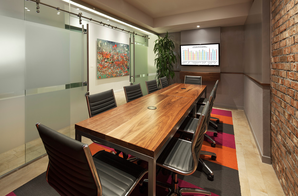 Hotel conference room with walnut and steel table and leather conference chairs