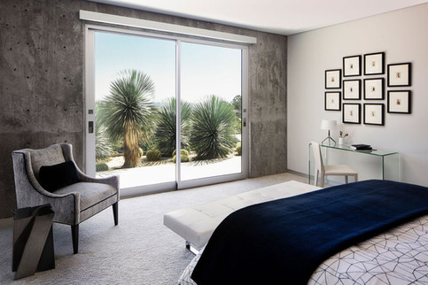 Modern Oasis bedroom with view of cactus through glass doors, with glass desk and velvet arm chair