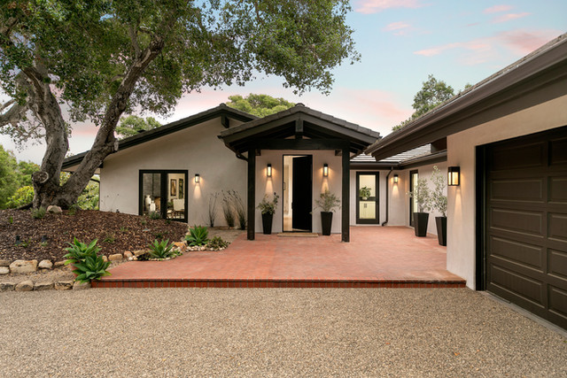 California ranch home exterior showing entry with brick patio and tree