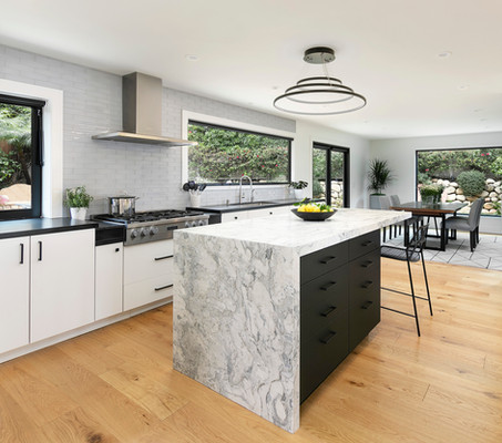 Modern kitchen with white cabinets and black island with marble top and waterfall edge. Light oak wood floors