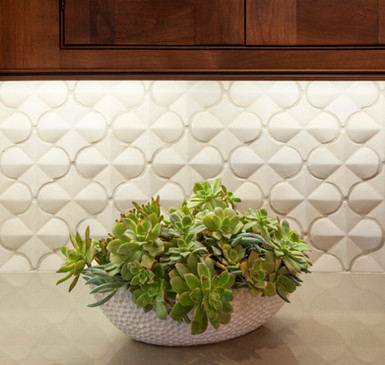 White 3-dimensional arabesque tile backsplash with dark wood cabinets and under cabinet lighting