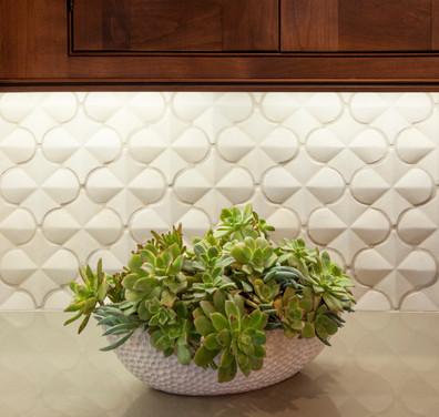 White 3-dimensional arabesque tile backsplash with dark wood cabinets and under cabinet lighting