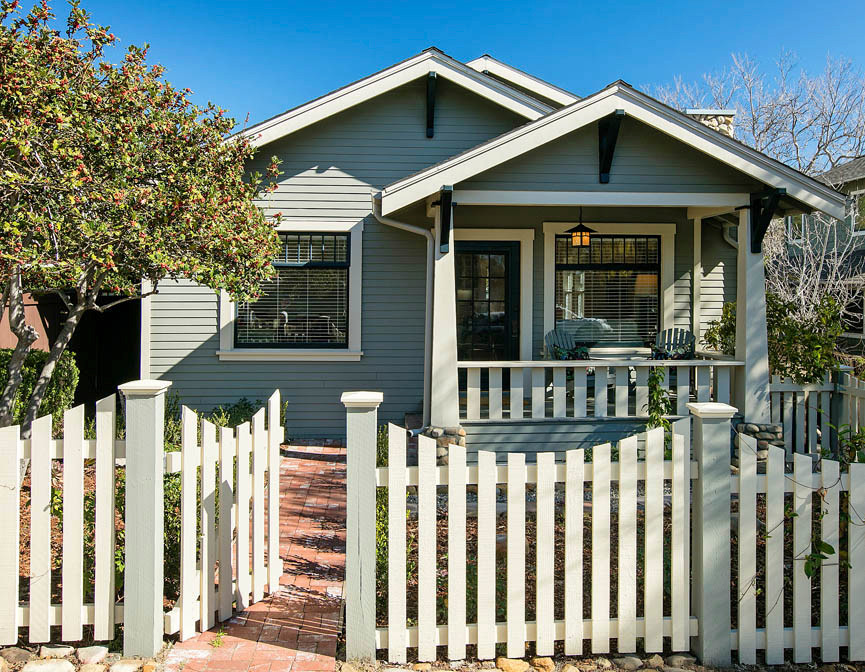 1917 Bungalow Haven exterior with picket fence and front porch