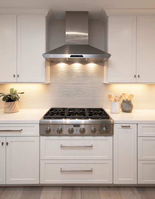 Kitchen built-in range with white shaker cabinets and stainless steel vent hood. 3-dimensional tile backsplash