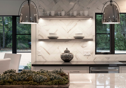 White kitchen with open shleving with under cabinet lighting and marble herringbone tile