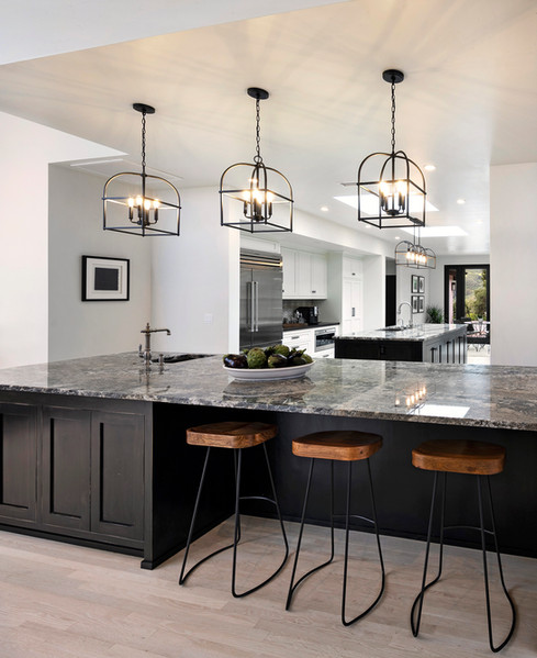 large wet bar island with painted black Shaker cabinets and three bar stools and penand lights