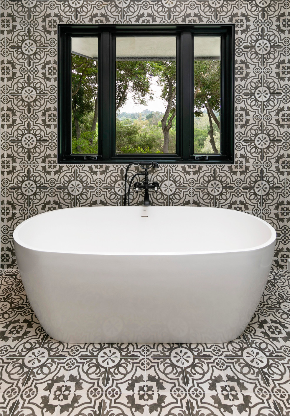 Freestanding soaking tub with patterened tile floor and wall in black and white with black window frame