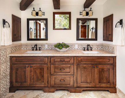 Spanish Mediterranean custom wood cabinetry vanity dual sinks, hand painted tile wainscotting, limestone floors, oil rubbed bronze and iron finishes on lighting and faucets