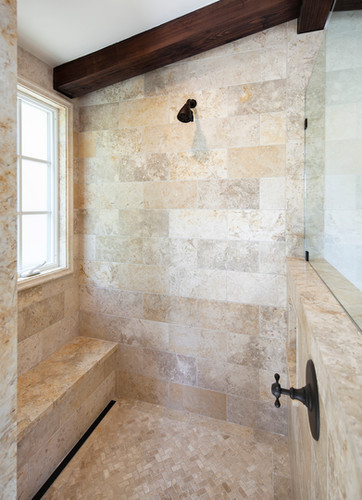 Spanish Mediterranean limestone tile shower with bench, infinity drain and window