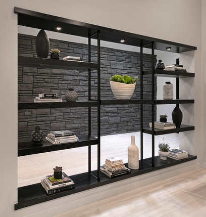 Open built in divider bookcase wall painted black with black flagstone behind