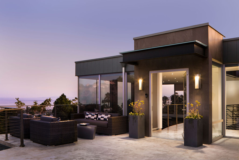Modern Oasis house entry patio and door at dusk with woven patio furniture