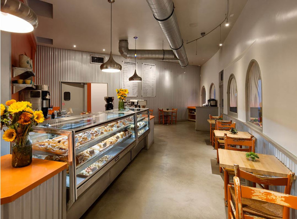 Corner Cafe with seating and display area. Orange accents and concrete floors